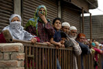 Kashmiri villagers watch funeral procession of top rebel commander Naseer Pandith, in Pulwama, south of Srinagar, Indian controlled Kashmir, Thursday, May 16, 2019. Three rebels, an army soldier and a civilian were killed early Thursday during a gunbattle in disputed Kashmir that triggered anti-India protests and clashes, officials and residents said. (AP Photo/ Dar Yasin)