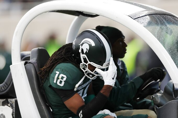 CORRECTS TO FELTON DAVIS III, NOT KALON GERVIN - Michigan State wide receiver Felton Davis III is carted off the field during the first half of an NCAA college football game against Michigan, Saturday, Oct. 20, 2018, in East Lansing, Mich. (AP Photo/Carlos Osorio)