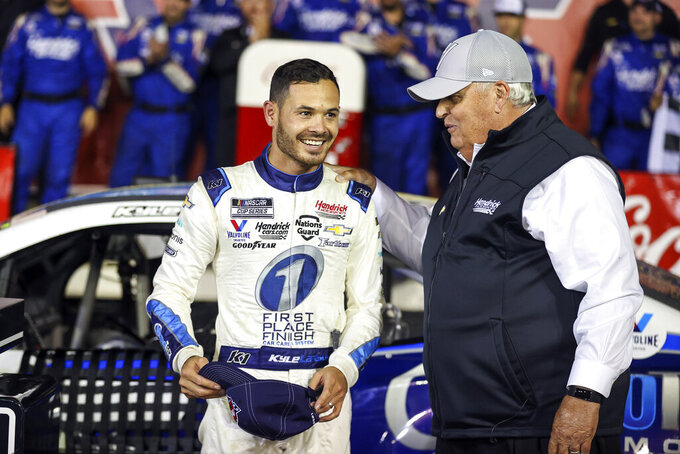 """FILE - Car owner Rick Hendrick, right, congratulates Kyle Larson in victory lane after Larson won the NASCAR Cup Series auto race at Charlotte Motor Speedway in Concord, N.C., in this Sunday, May 30, 2021, file photo. With few companies willing to back Larson upon his return from a nearly yearlong suspension for using a racial slur, Rick Hendrick put the website for his dealerships on the hood of Larson's car. Larson started winning races, which company officials say drove traffic to HendrickCars.com that netted $1.8 million in leads and over $5 million in television exposure.  """"We're having the best year we've ever had,"""" said Hendrick, owner of the largest privately held dealership in the country. """"The market is blazing."""" (AP Photo/Nell Redmond, File)"""