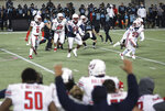 Liberty players celebrate after defeating Coastal Carolina in overtime with a blocked field goal in the Cure Bowl NCAA college football game Saturday, Dec. 26, 2020, in Orlando, Fla. (AP Photo/Matt Stamey)