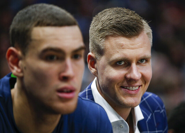 Dallas Mavericks forwards Kristaps Porzingis, right, and Dwight Powell watch from the bench during the first half of the team's NBA basketball game against the Portland Trail Blazers, Friday, Jan. 17, 2020, in Dallas. (AP Photo/Brandon Wade)