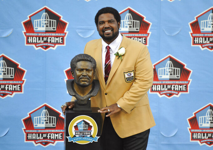 FILE - In this Aug. 3, 2013, file photo, Jonathan Ogden poses with his bust during the induction ceremony at the Pro Football Hall of Fame in Canton, Ohio. After moving from Cleveland to Baltimore, the Ravens used the first draft pick in franchise history to take Ogden with the fourth overall selection in 1996. (AP Photo/David Richard, File)