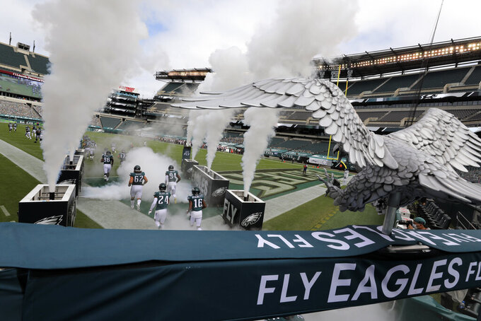 Philadelphia Eagles players run onto the field before an NFL football game against the Cincinnati Bengals, Sunday, Sept. 27, 2020, in Philadelphia. (AP Photo/Laurence Kesterson)