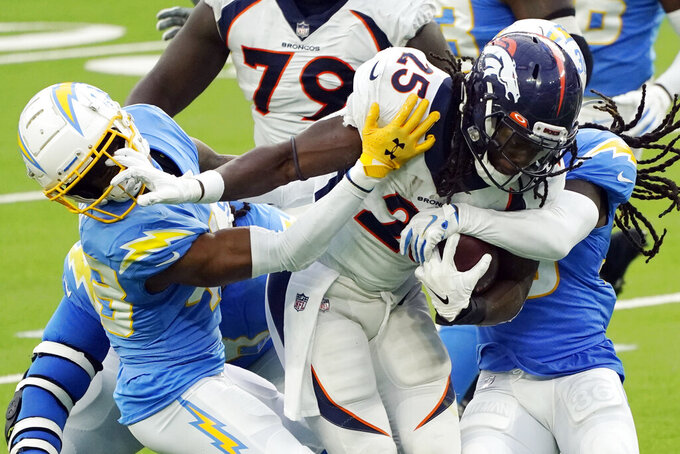 Denver Broncos running back Melvin Gordon (25) is tackled by Los Angeles Chargers cornerback Michael Davis, left, during the second half of an NFL football game Sunday, Dec. 27, 2020, in Inglewood, Calif. (AP Photo/Ashley Landis)