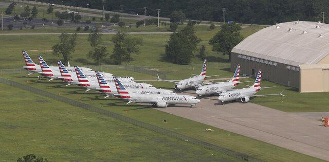 In a May 24, 2019 aerial photo, American Airlines 737 Max are stored at Tulsa International Airport. Boeing Co. said Monday, Dec. 16, 2019 that it will temporarily stop producing its grounded 737 Max jet starting in January 2020 as it struggles to get approval from regulators to put the plane back in the air. (Tom Gilbert/Tulsa World via AP)