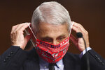 Dr. Anthony Fauci, director of the National Institute for Allergy and Infectious Diseases, lowers his face mask as he prepares to testify before a Senate Health, Education, Labor and Pensions Committee hearing on Capitol Hill in Washington, Tuesday, June 30, 2020. (Kevin Dietsch/Pool via AP)