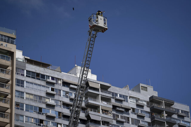 "Firefighter Elielson Silva plays his trumpet on the top of a ladder for residents cooped up at home, during a lockdown to help contain the spread of the new coronavirus in Rio de Janeiro, Brazil, Sunday, April 5, 2020. As he played in several Rio neighborhoods on Sunday, his final numbers were Brazil's national anthem, then ""Hallelujah."" (AP Photo/Leo Correa)"