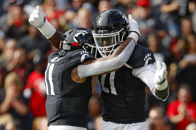 Cincinnati defensive end Myjai Sanders (21) celebrates with linebacker Bryan Wright (11) after sacking Tulsa quarterback Zach Smith during the first half of an NCAA college football game, Saturday, Oct. 19, 2019, in Cincinnati. (AP Photo/John Minchillo)