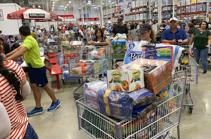 FILE - In this Aug. 29, 2019, photo shoppers wait in long lines at Costco in Davie, Fla. On Thursday, Sept. 12, the Labor Department reports on U.S. consumer prices for August. (AP Photo/Brynn Anderson, File)