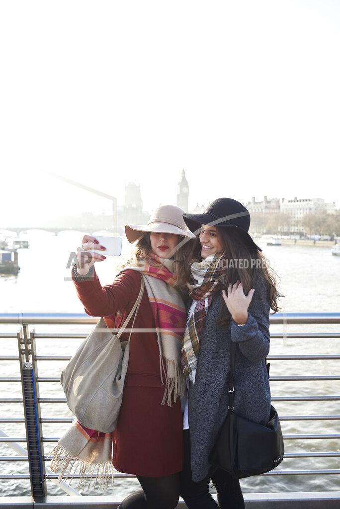 UK, London, two women taking a selfie on Millennium Bridge with cityscape in background