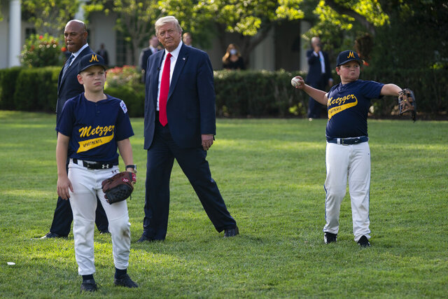 President Donald Trump walks with New York Yankees Hall of Fame pitcher Mariano Rivera as he greets youth baseball players on the South Lawn of the White House to mark Opening Day for Major League Baseball, Thursday, July 23, 2020, in Washington. (AP Photo/Evan Vucci)