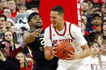 North Carolina State's Jericole Hellems, right, charges into Florida State's M.J. Walker, left, for a foul during the second half of an NCAA college basketball game in Raleigh, N.C., Saturday, Feb. 22, 2020. (AP Photo/Karl B DeBlaker)