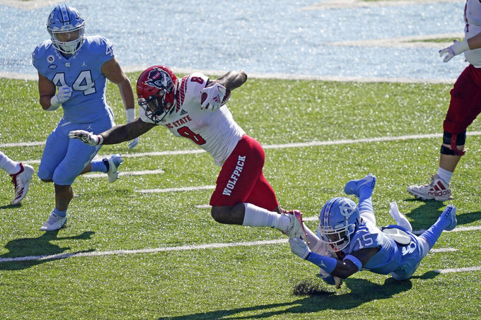 North Carolina defensive back DeAndre Hollins (15) reaches for North Carolina State running back Ricky Person Jr. (8) during the first half of an NCAA college football game in Chapel Hill, N.C., Saturday, Oct. 24, 2020. (AP Photo/Gerry Broome)