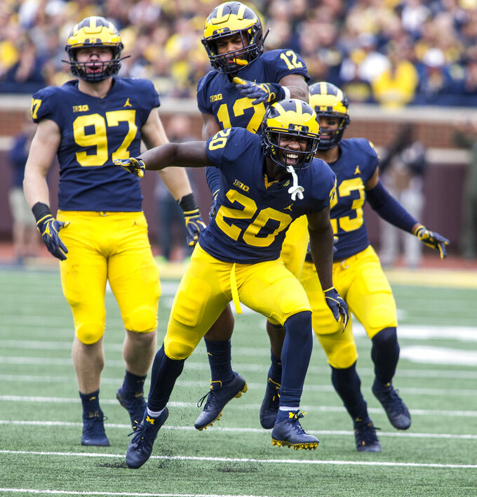 FILE - In this Sept. 8, 2018, file photo, Michigan defensive back Brad Hawkins (20) celebrates a tackle with teammates Aidan Hutchinson (97), Josh Ross (12), and Tyree Kinnel (23), in the third quarter of an NCAA college football game against Western Michigan, in Ann Arbor, Mich. Michigan's defense, which returned nine starters from the unit that ranked No. 3 in the nation last year, play Nebraska on Saturday. (AP Photo/Tony Ding, File)