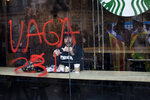 A man eats inside a coffeeshop with a glass painted with a graffiti reading in Catalan:
