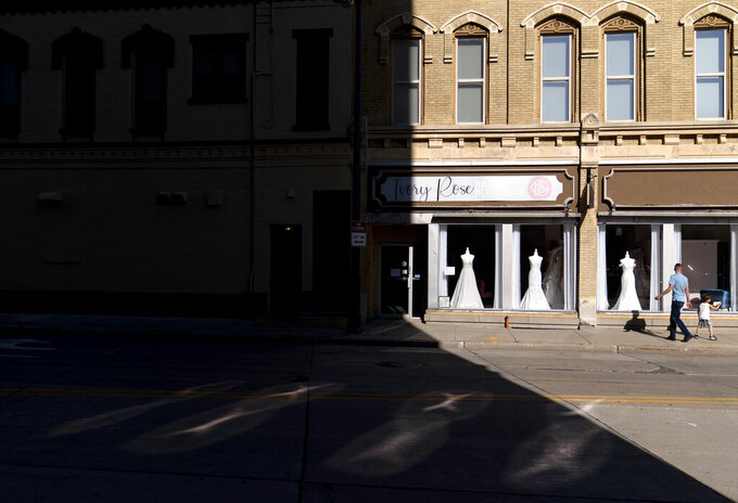 A father and son walk past a wedding gown shop in Appleton, Wis., Aug. 19, 2020. The downtown had been evolving as young parents moved back to Wisconsin from Minneapolis and Chicago, just to raise kids and open a business. Restaurants and boutiques popped up along College Avenue, catering to the professors and students at Lawrence University. Then the pandemic struck. (AP Photo/David Goldman)