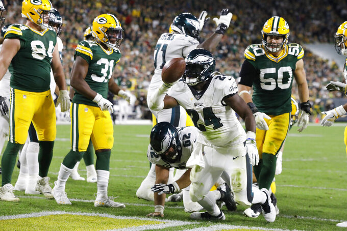 Philadelphia Eagles running back Jordan Howard holds up the ball after running in for a touchdown during the second half of the team's NFL football game against the Green Bay Packers on Thursday, Sept. 26, 2019, in Green Bay, Wis. (AP Photo/Mike Roemer)