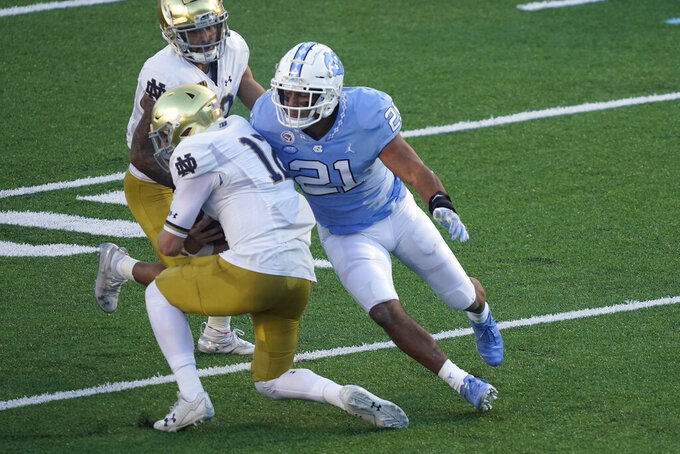 North Carolina linebacker Chazz Surratt (21) sacks Notre Dame quarterback Ian Book (12) during the first half of an NCAA college football game in Chapel Hill, N.C., Friday, Nov. 27, 2020. (AP Photo/Gerry Broome)