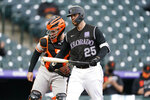 Colorado Rockies' C.J. Cron, front, reacts after striking out as San Francisco Giants catcher Buster Posey looks on in the seventh inning of game one of a baseball doubleheader Tuesday, May 4, 2021, in Denver. (AP Photo/David Zalubowski)