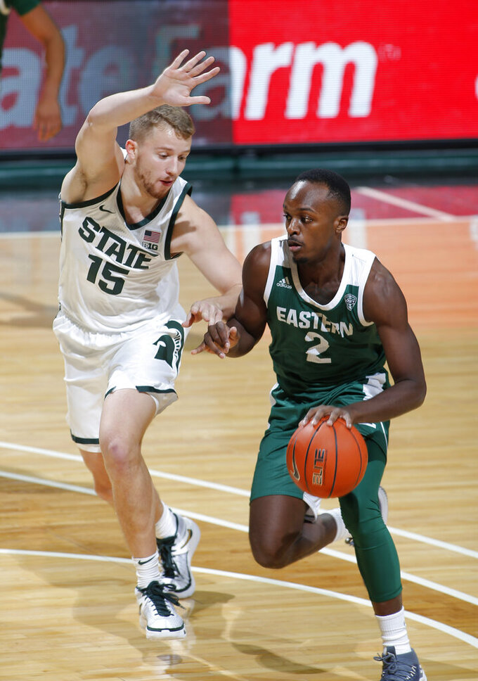 Eastern Michigan's Miles Gibson, right, drives against Michigan State's Thomas Kithier (15) during the first half of an NCAA college basketball game, Wednesday, Nov. 25, 2020, in East Lansing, Mich. (AP Photo/Al Goldis)
