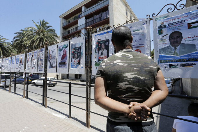 A man looks at electoral posters in Algiers, Wednesday, June 9, 2021. Algerians are preparing for the June 12 elections to elect members of parliament. (AP Photo/Toufik Doudou)
