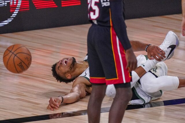 Milwaukee Bucks' Giannis Antetokounmpo reacts after hurting his ankle during the first half of an NBA conference semifinal playoff basketball game against the Miami Heat Sunday, Sept. 6, 2020, in Lake Buena Vista, Fla. (AP Photo/Mark J. Terrill)