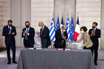 From the left, Greek Prime Minister Kyriakos Mitsotakis, Greek Defence Minister Nikolaos Panagiotopoulos, Greek Foreign Affairs Minister Nikos Dendias, French Foreign Affairs Minister Jean-Yves Le Drian, French Defense Minister Florence Parly and French President Emmanuel Macron applause before the signing ceremony of a new defence deal at The Elysee Palace Tuesday, Sept. 28, 2021. France and Greece announced on Tuesday a major, multibillion-euro defense deal including Athens' decision to buy three French warships. (Ludovic Marin, Pool Photo via AP)