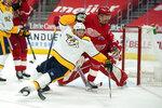 Detroit Red Wings defenseman Jon Merrill (24) checks Nashville Predators center Calle Jarnkrok (19) in the first period of an NHL hockey game Thursday, April 8, 2021, in Detroit. (AP Photo/Paul Sancya)