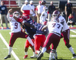 Massachusetts quarterback Garrett Dzuro (9) makes a pass under pressure during the first half of an NCAA college football game against Liberty on Friday, Nov. 27, 2020, at Williams Stadium in Lynchburg, Va. (AP Photo/Shaban Athuman)