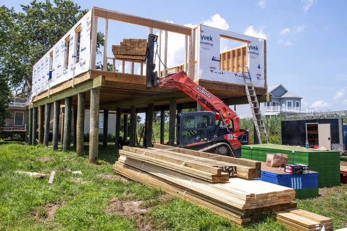 Lumber is lifted at at a construction site Frederica, Del. While demand for new homes are high, local builders and suppliers says prices for materials, especially lumber, are soaring. (Marc Clery/Delaware State News via AP)