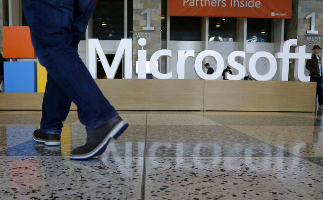 FILE - In this April 28, 2015, file photo, a man walks past a Microsoft sign set up for the Microsoft BUILD conference at Moscone Center in San Francisco. A federal judge says it's likely that Microsoft was trying to avoid or evade paying U.S. taxes and is ordering the company to hand over financial documents from more than a decade ago. (AP Photo/Jeff Chiu, File)