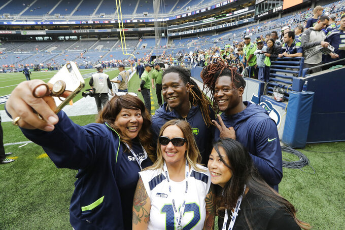 Fans pose for a photo with Seattle Seahawks cornerback Shaquill Griffin, right, and his brother, linebacker Shaquem Griffin, second from right, before the team's NFL football preseason game against the Denver Broncos, Thursday, Aug. 8, 2019, in Seattle. (AP Photo/Elaine Thompson)