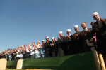 Relatives and friends of the victims, with religious leaders pray at a soccer stadium in Kozarac near the town of Prijedor, behind the coffins draped with green cloth for the funeral of 86 Muslims, Saturday July 20, 2019.  The victims were slain by Serbs in one of the worst atrocities of the country's 1992-95 war, aged 19 to 61, and were among some 200 Bosnian Muslims and Croats from Prijedor who were executed in Aug. 1992 on a cliff on Mt. Vlasic known as Koricanske Stijene. (AP Photo/Almir Alic)
