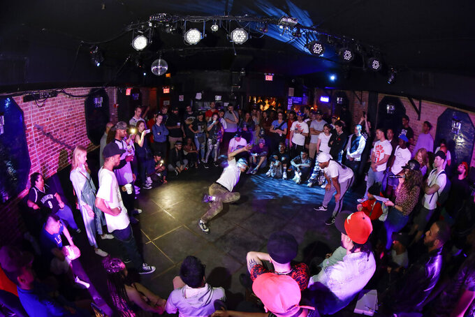 People watch breakers during a competition hosted by Supreme Beingz at the Mercury Lounge Friday, June 7, 2019, in New York.  Many in the breaking community are eager for the art form to expand its audience after the International Olympic Committee announced that it would become an official sport at the Paris 2024 games. But that optimism is hardly unanimous. (AP Photo/Frank Franklin II)