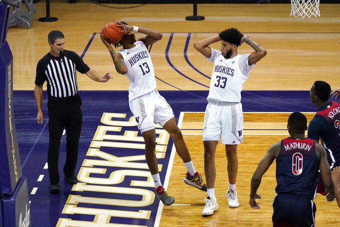 Washington's Hameir Wright (13) works to keep the ball inbounds for the Huskies against Arizona as teammate J'Raan Brooks looks on in the second half of an NCAA college basketball game Thursday, Dec. 31, 2020, in Seattle. Wright was successful on the play, but Arizona won 80-53. (AP Photo/Elaine Thompson)