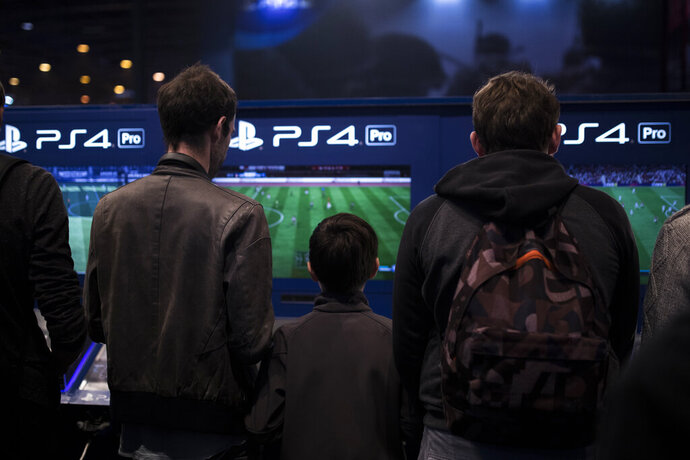 In this Nov. 3, 2017, photo, visitors play FIFA 18 video game on Playstation 4 Pro (PS4) at the Paris Games Week in Paris. Gaming is going green. Companies behind PlayStation, Xbox, Angry Birds, Minecraft, Twitch and other video games and platforms pledged Monday, Sept. 23, 2019, at the U.N. to level up efforts to fight climate change and get their throngs of users involved. (AP Photo/Kamil Zihnioglu)