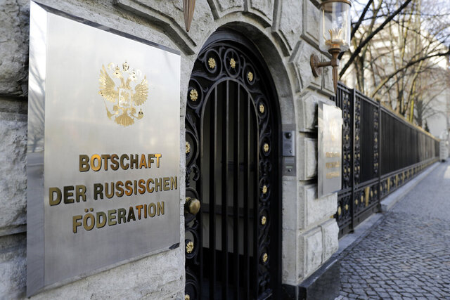 FILE- in this March 27, 2018 file photo a sign reading 'Emabassy of the Russian Federation' displayed at entrance of the Russian embassy in Berlin, Germany. Germany said Thursday it is seeking EU sanctions against a Russian man over his alleged role in the hacking of the German parliament at a time when evidence shows he was working for Russian intelligence. Germany's Foreign Ministry said it called in Russian ambassador Sergei Nechayev to inform him in person of the move. (AP Photo/Markus Schreiber)