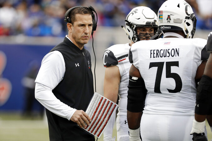Cincinnati head coach Luke Fickell talks with players during the first half of an NCAA college football game against Memphis, Friday, Nov. 29, 2019, in Memphis, Tenn. (AP Photo/Mark Humphrey)