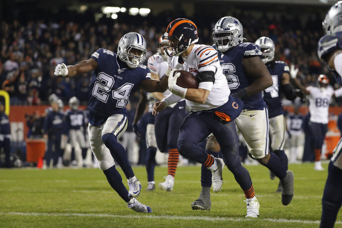 Chicago Bears quarterback Mitchell Trubisky (10) runs in for a touchdown against Dallas Cowboys' Chidobe Awuzie (24) during the second half of an NFL football game, Thursday, Dec. 5, 2019, in Chicago. (AP Photo/Morry Gash)