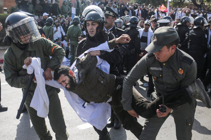 Security forces detain a protesting teacher during a demonstration in Rabat, Morocco, Wednesday, Feb. 20, 2019. Moroccan police fired water cannons at protesting teachers who were marching toward a royal palace and beat people with truncheons amid demonstrations around the capital Wednesday. (AP Photo/Mosa'ab Elshamy)