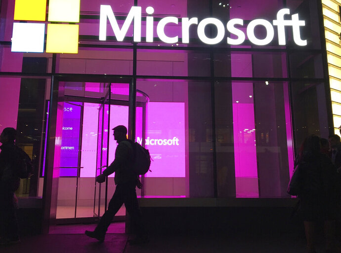 """FILE - In this Nov. 10, 2016, photo, people walk near a Microsoft office in New York.  Microsoft says Iranian hackers have posed as conference organizers in Germany and Saudi Arabia in an attempt to spy on """"high-profile"""" people using spoofed email invitations. The tech company said Wednesday, Oct. 28, 2020, it detected attempts by the hacking group it calls Phosphorus to trick former government officials, policy experts and academics.  (AP Photo/Swayne B. Hall)"""