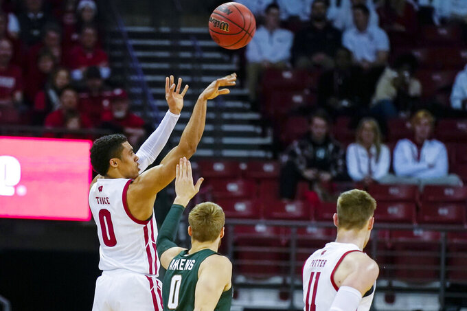 Wisconsin's D'Mitrik Trice (0) shoots a 3-point basket over Michigan State's Kyle Ahrens during the first half of an NCAA college basketball game Saturday, Feb. 1, 2020, in Madison, Wis. (AP Photo/Andy Manis)