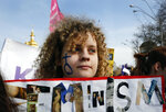 Ukrainian people hold banners and march on the occasion of the International Women's Day in Kiev, Ukraine, Friday, March 8, 2019. Millions across the globe are marking International Women's Day by demanding a gender-balanced world amid persistent salary gap, violence and widespread inequality. (AP Photo/Efrem Lukatsky)