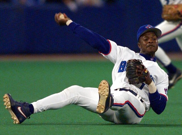 FILE - In this Sept. 17, 1999, file photo, Toronto Blue Jays third baseman Tony Fernandez throws to first as he tumbles to the turf during third-inning AL action against the Chicago White Sox in Toronto.  Former All-Star shortstop Fernandez remained on a life support system Sunday, Feb. 16, 2020, pending a decision by his family on how to proceed, the director of his foundation said. He had been in a medically induced coma, said Imrad Hallim, the director and co-founder of the Tony Fernández Foundation. Fernandez was ill with a kidney disease for years and waiting for a transplant. (Frank Gunn/The Canadian Press via AP, File)