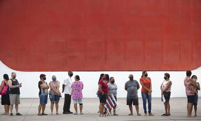 People wait in line to get the Sinovac vaccine at a COVID-19 vaccination point for seniors in Duque de Caxias, Brazil, Wednesday, March 24, 2021. (AP Photo/Silvia Izquierdo)