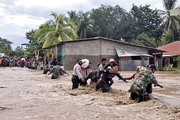 In this image made from video, soldiers and police officers assist residents to cross a flooded road in Malaka Tengah, East Nusa Tenggara province, Indonesia, Monday, April 5, 2021. Multiple disasters caused by torrential rains in eastern Indonesia have left dozens of people dead and missing and displaced thousands, the country's disaster relief agency said Monday. (AP Photo)
