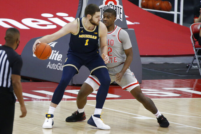 Michigan's Hunter Dickinson, left, posts up against Ohio State's E.J. Liddell during the first half of an NCAA college basketball game Sunday, Feb. 21, 2021, in Columbus, Ohio. (AP Photo/Jay LaPrete)