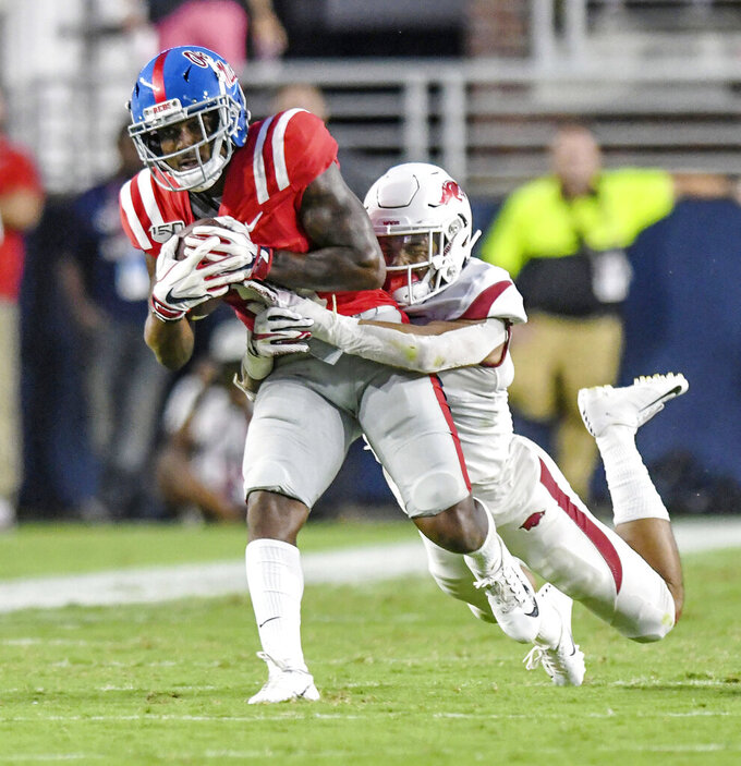 Mississippi wide receiver Elijah Moore (8) is tackled by Arkansas defensive back Greg Brooks Jr. (9) during the first half of an NCAA college football game, Saturday, Sept. 7, 2019, in Oxford, Miss. (Bruce Newman/The Oxford Eagle via AP)