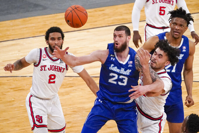 Seton Hall forward Sandro Mamukelashvili (23) and St. John's forward Arnaldo Toro, right, fight for a loose ball during the first half of an NCAA college basketball game in the quarterfinals of the Big East conference tournament, Thursday, March 11, 2021, in New York. (AP Photo/Mary Altaffer)