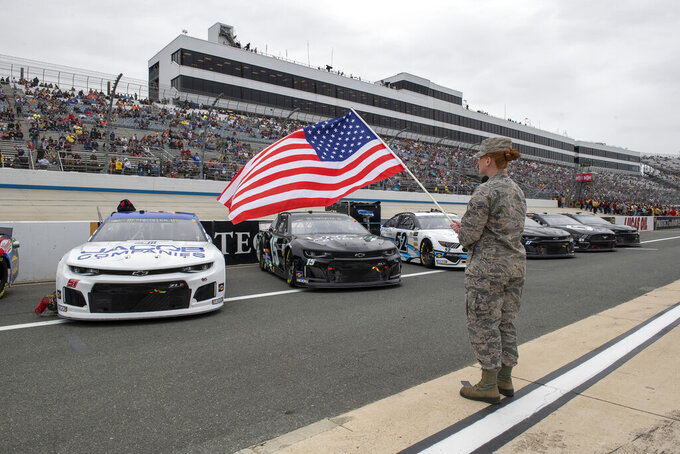 A1C Brittney Hughes with the Delaware National Guard presenting an American flag at the Drydene 400 - Monster Energy NASCAR Cup Series playoff auto race, Sunday, Oct. 6, 2019, at Dover International Speedway in Dover, Del. (AP Photo/Jason Minto)